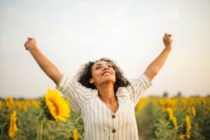 Frau steht im Sonnenblumenfeld und streckt Arme vor Freude nach Oben