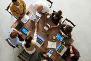 Menschen sitzen am Tisch und arbeiten